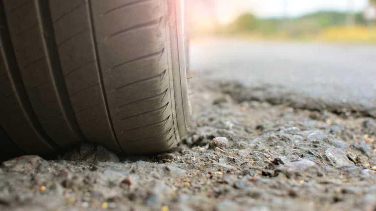 Car tyre on a broken asphalt road