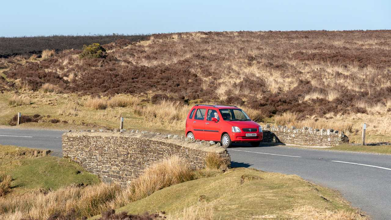 Car passing over a stone built bridge in Exmoor National Park England
