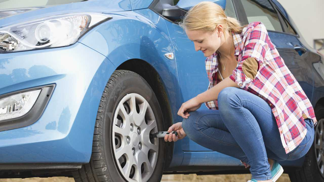 Woman checking car tyre pressure