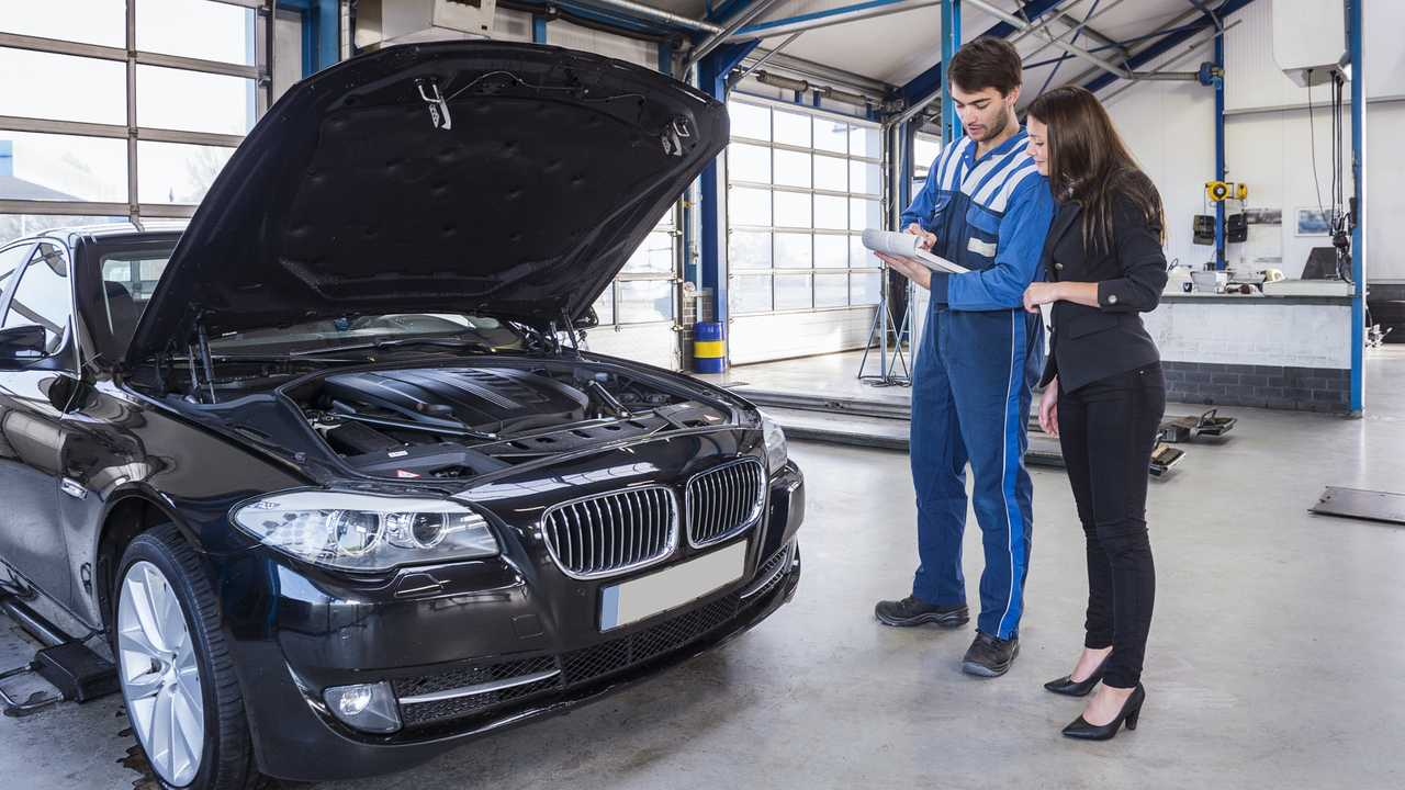 Car mechanic and customer in service garage going through checklist
