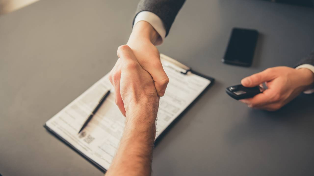 Men shaking hands while signing documents at car dealership