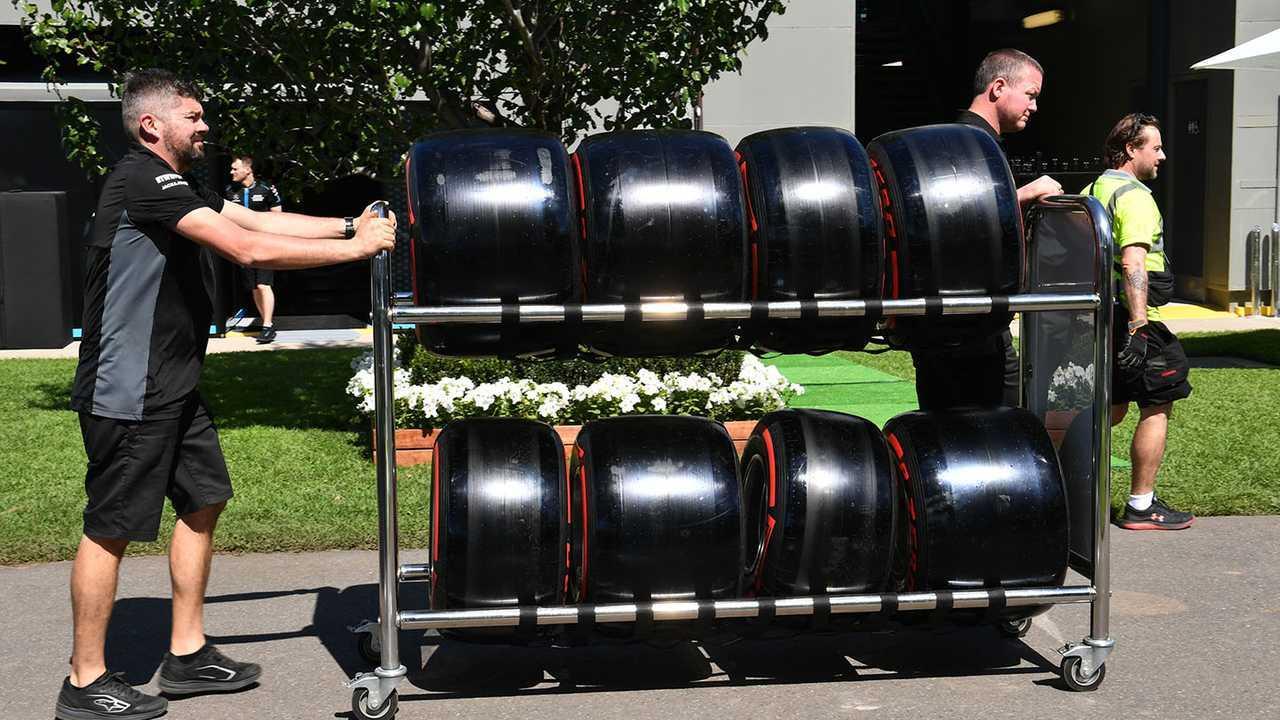 Pirelli personnel wheel tyres through the paddock