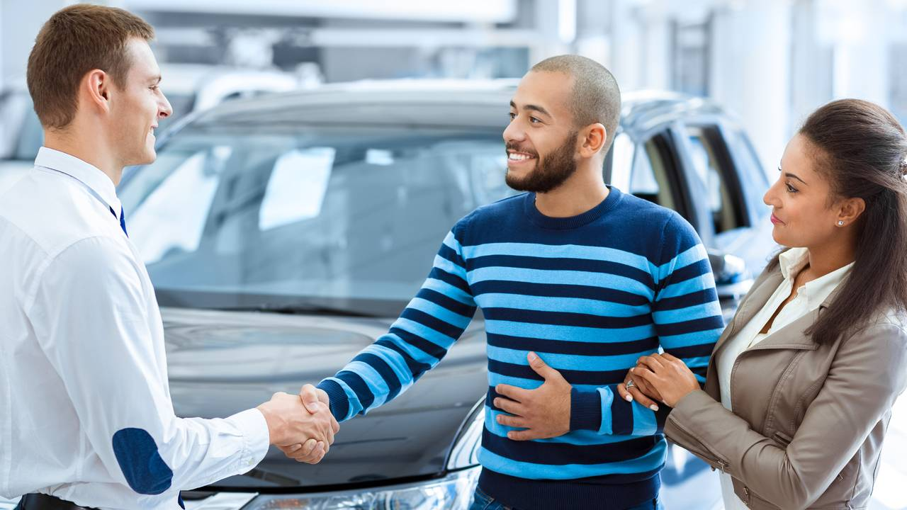 Couple buying new car shaking hands with salesman at car dealership |  InsideEVs Photos