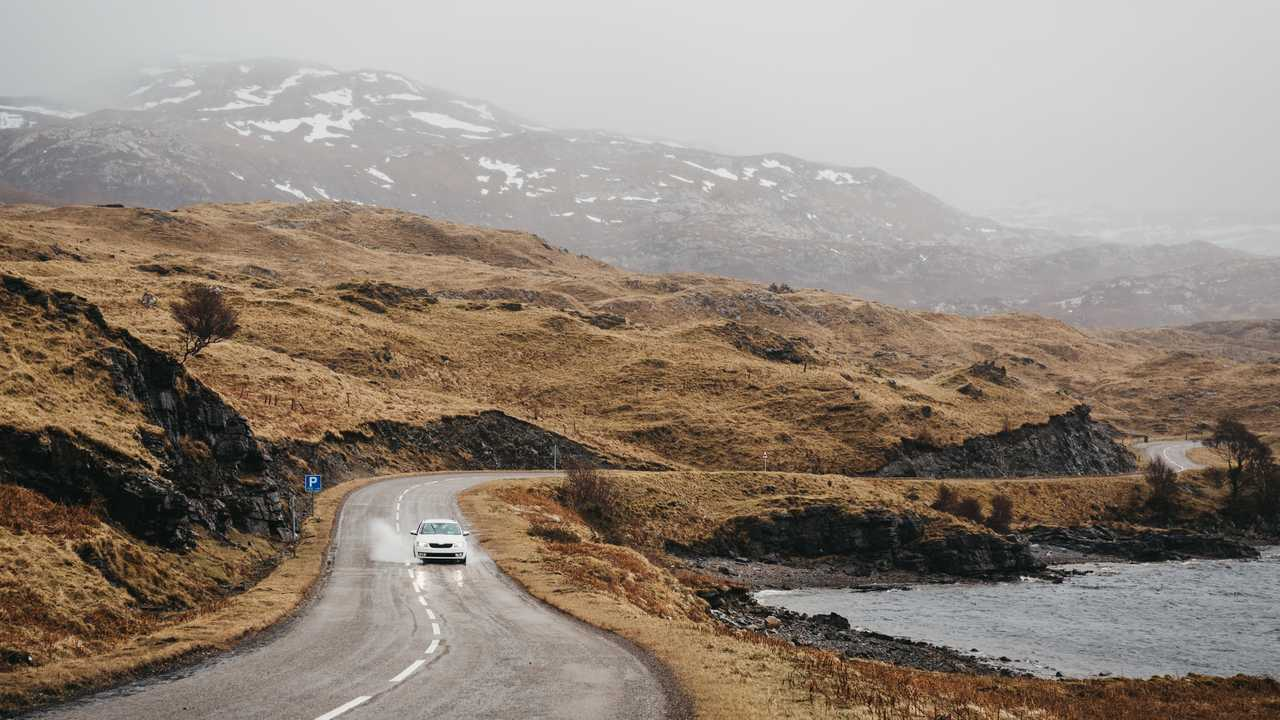 Car driving through Scottish Highlands near Lochinver on a foggy day