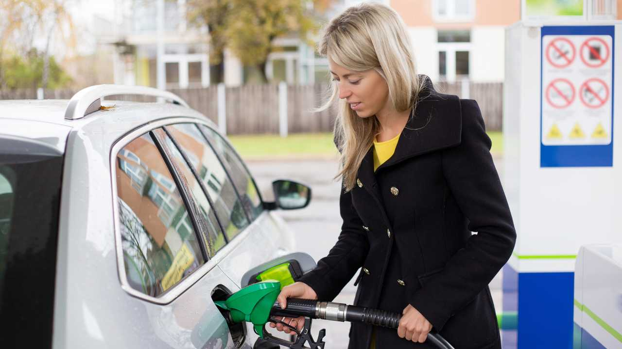 Woman refuelling at petrol station