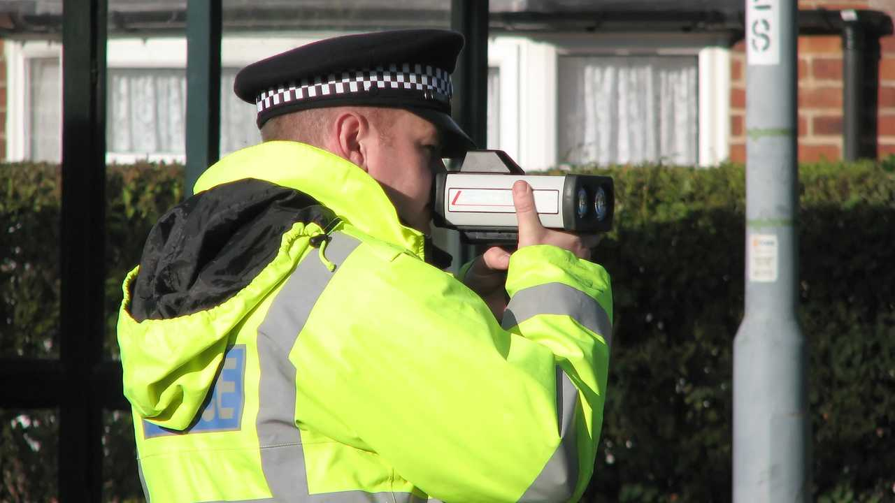 Policeman using hand held speed camera on UK road