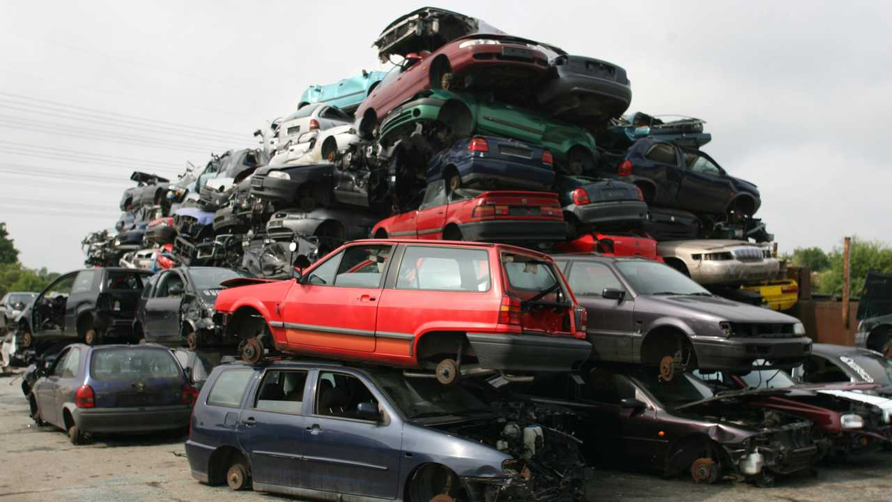 Stacked and crushed old cars in junkyard