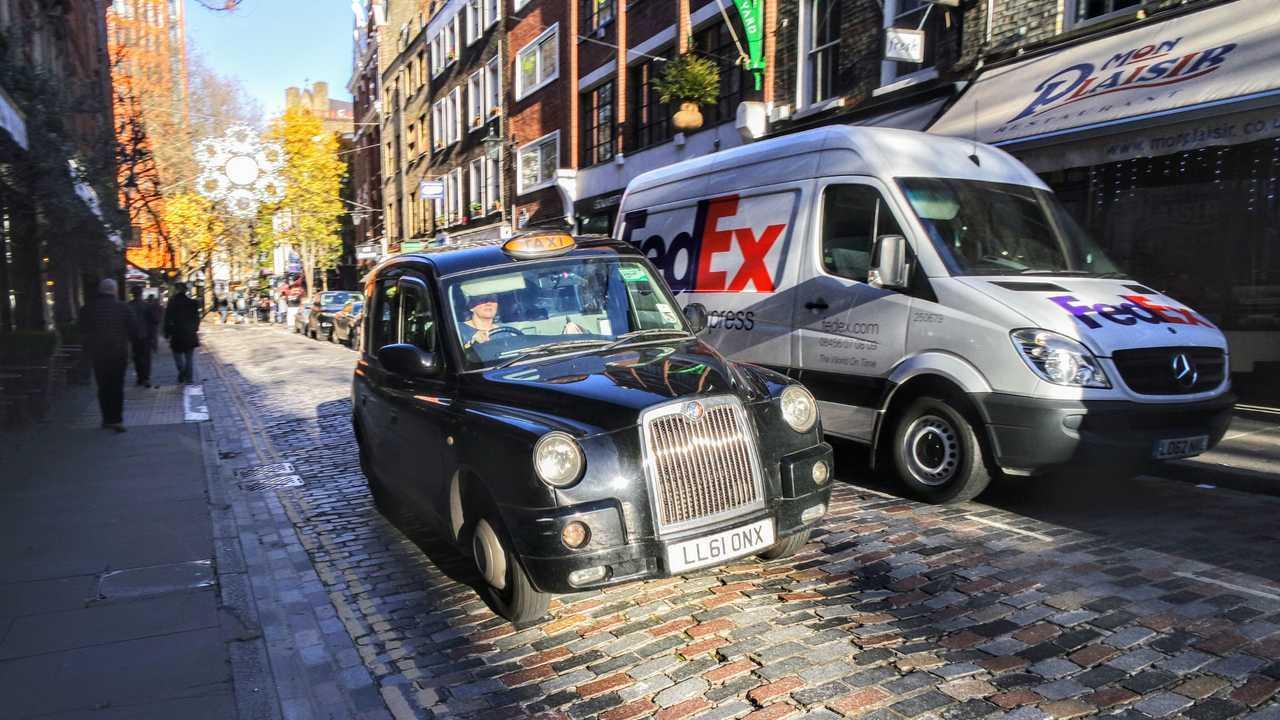 Taxi with FedEx van on brick road in London