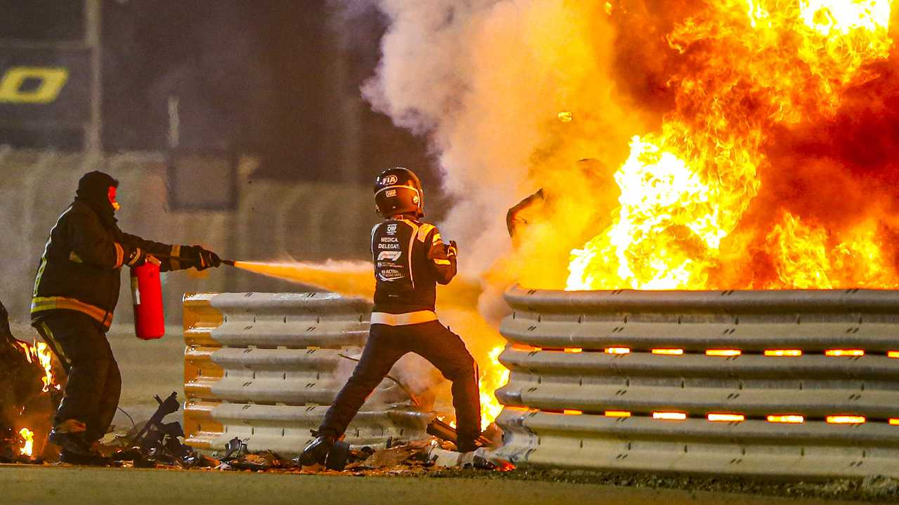 Fire marshals deal with the flames and a medical delegate assists Romain Grosjean, Haas F1, after a huge crash on the opening lap