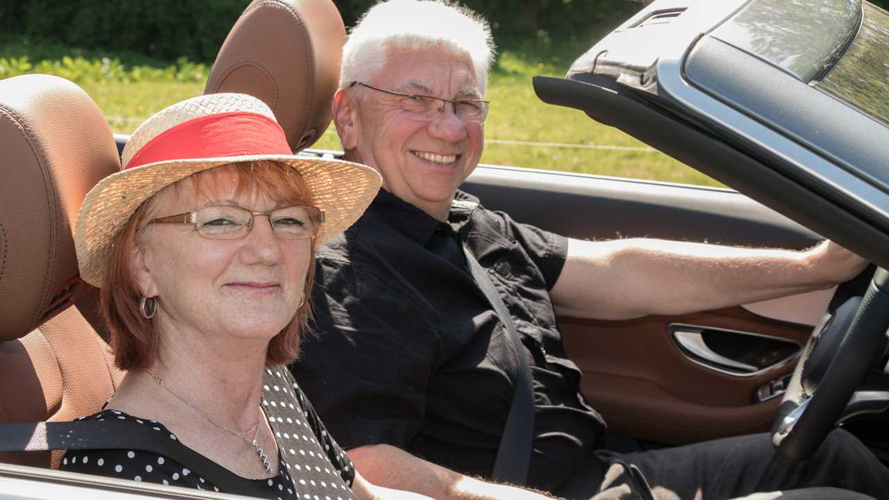 Smiling happy senior couple in the car on a sunny day
