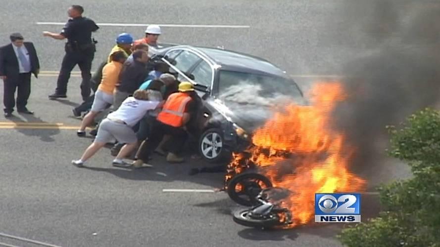 Heroic bystanders lift flaming car off injured motorcyclist