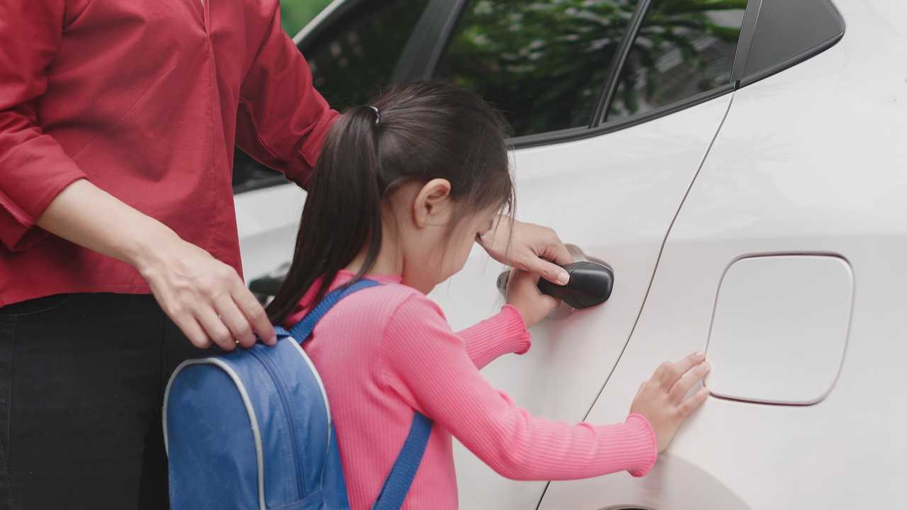Mother helping daughter into car to drive to school