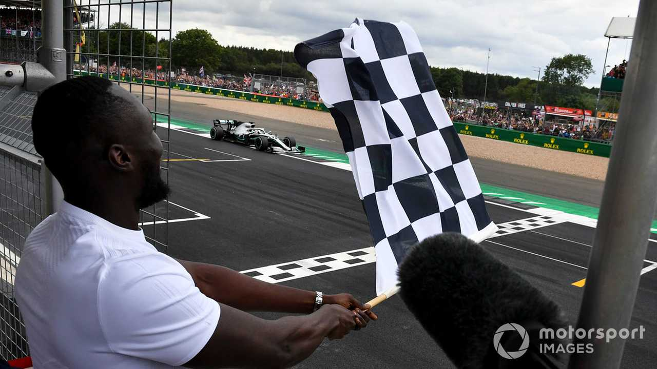 Rapper Stormzy waves finish flag for Lewis Hamilton at British GP 2019