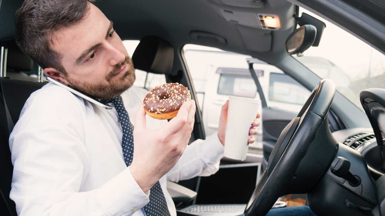 Businessman eating donut and drinking while using phone in his car