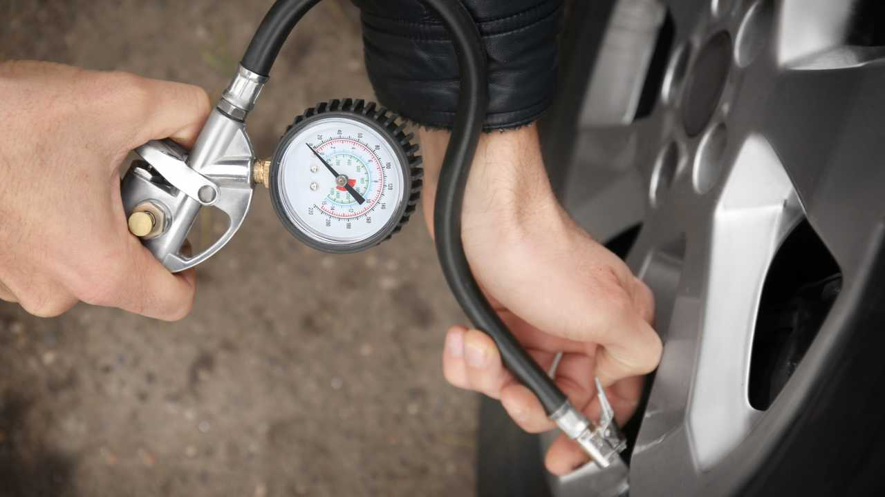 Auto mechanic checking tyre pressure