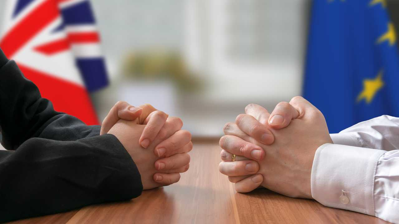 Clasped hands in mock Brexit negotiation of UK and EU politicians
