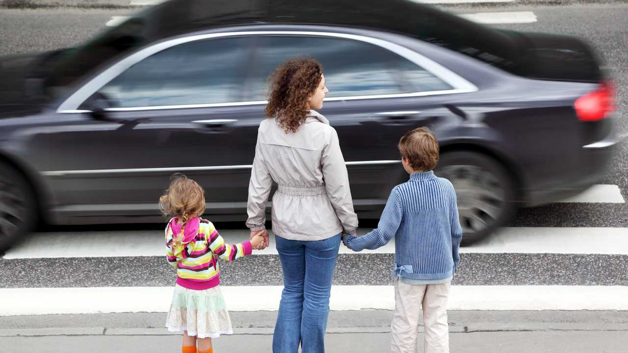 Mother with children at crosswalk facing busy road