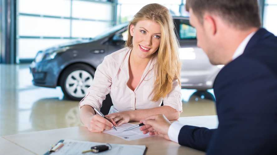Woman with car salesman signing document