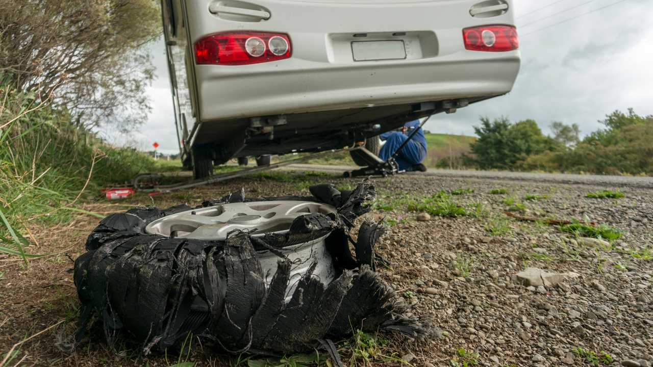 Caravan flat tyre on side of road with roadside assistance changing the tyre