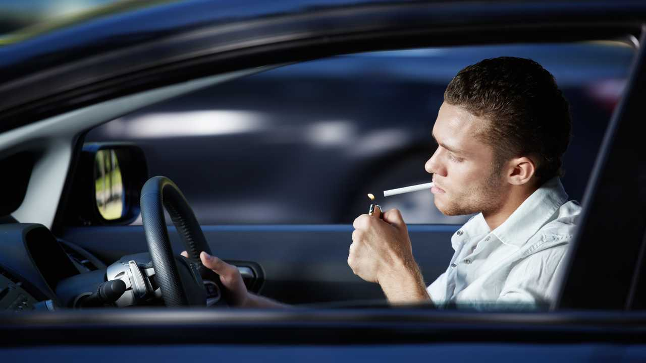 Man lights cigarette in car while driving