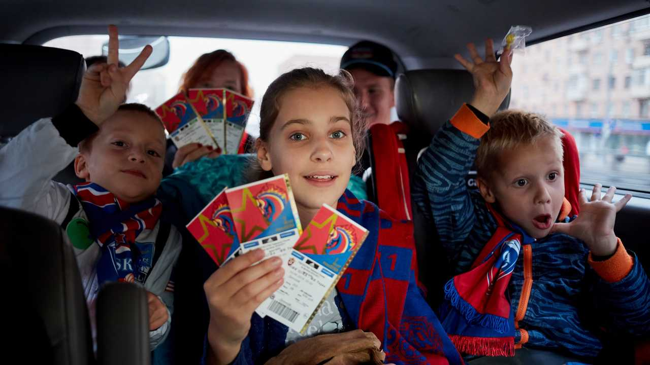 Family with children in car show tickets for football match