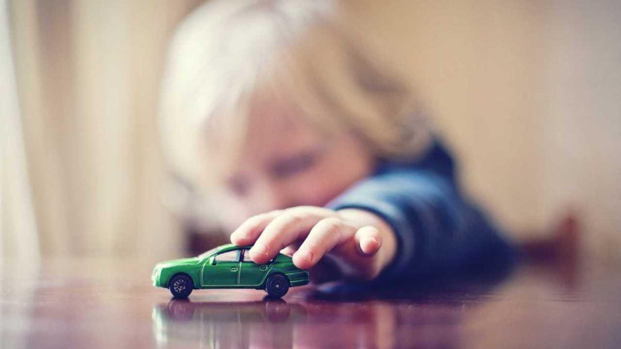 Un enfant joue avec une petite voiture