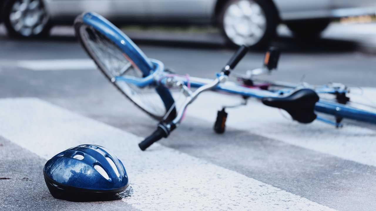 Helmet and bike lying on the road on a pedestrian crossing