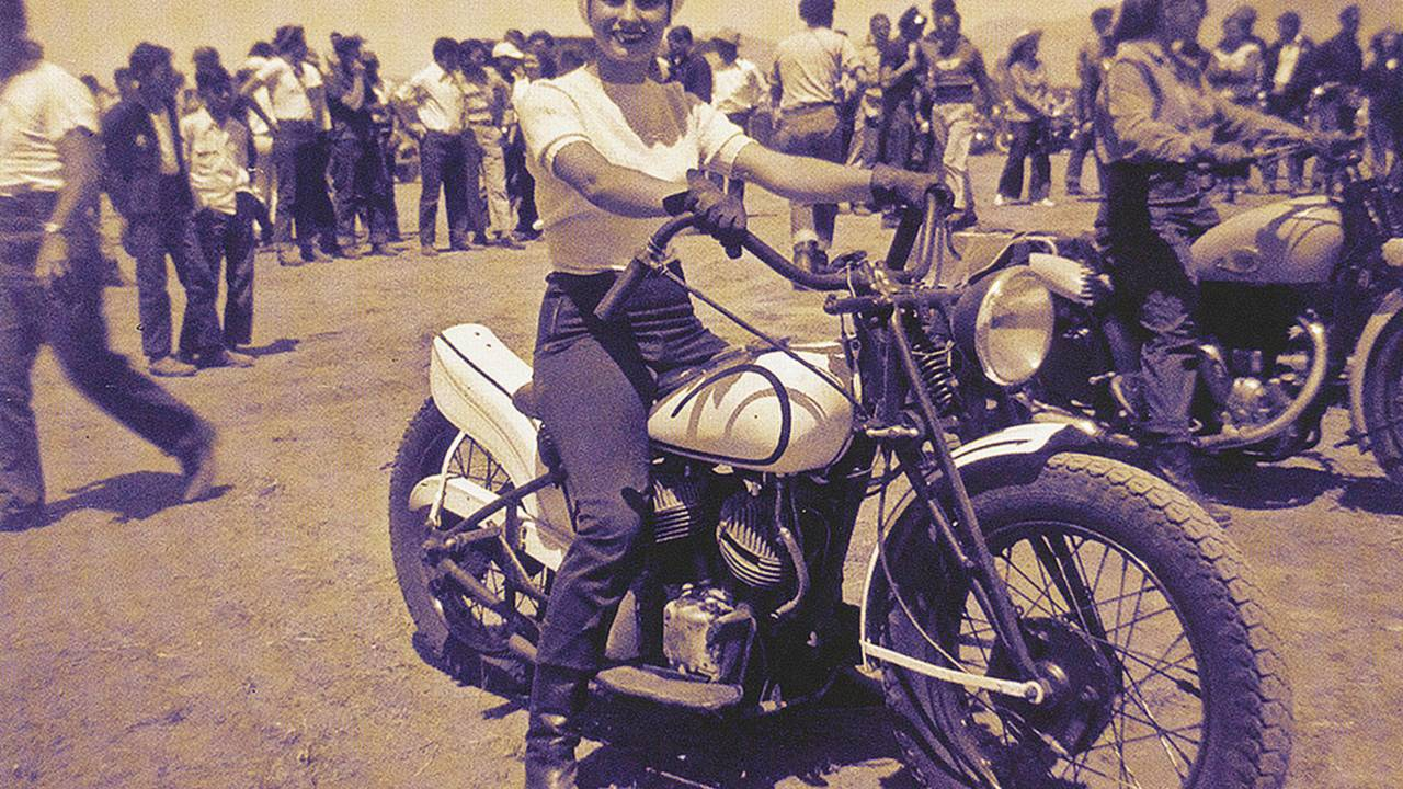 <strong>Patti posing for a picture at the starting line of an enduro in California on her Indian bobber.</strong>