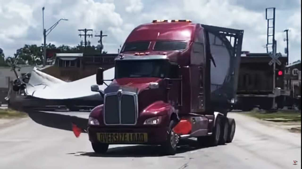 Screenshot of a video showing a train hitting a truck pulling a wind turbine blade.