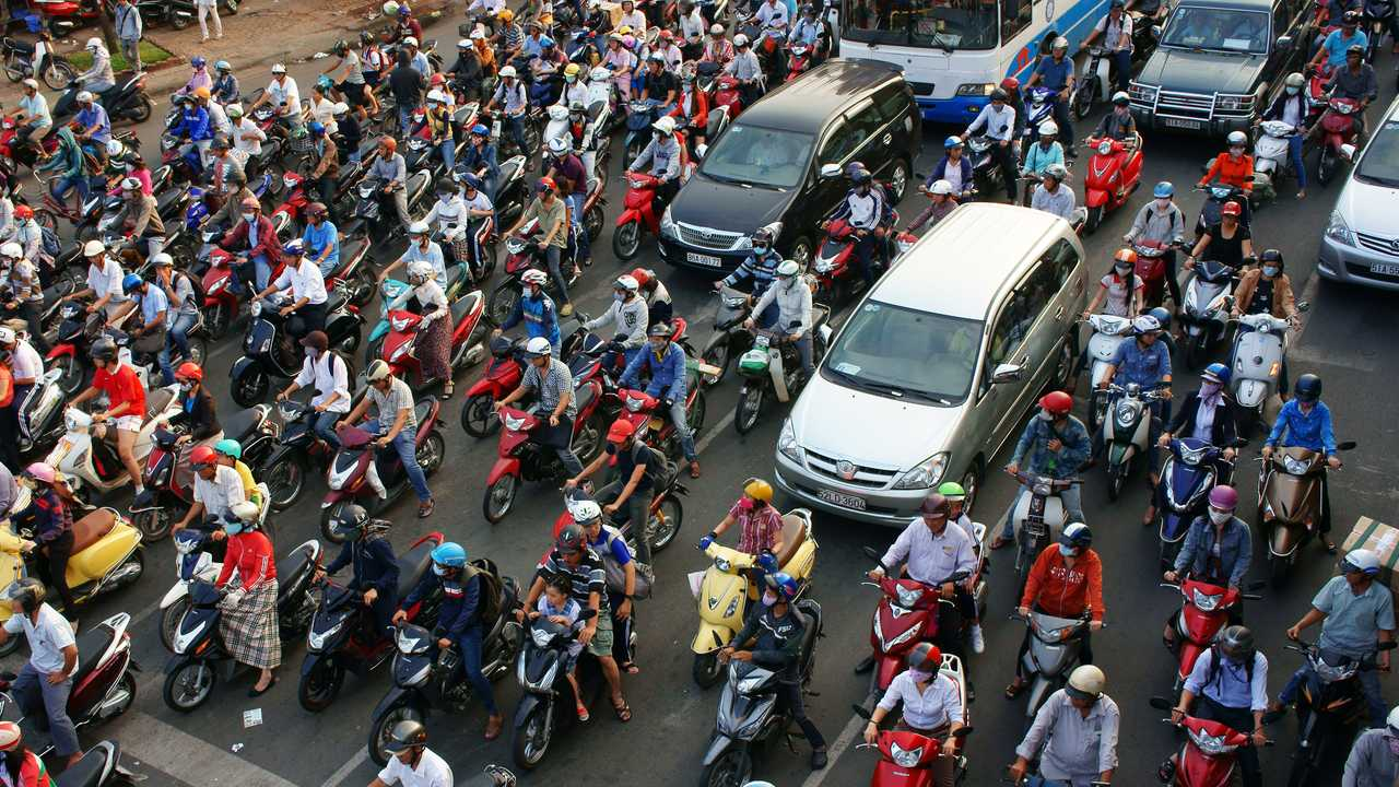 Heavy traffic with people mostly riding motorcycles Hanoi Vietnam