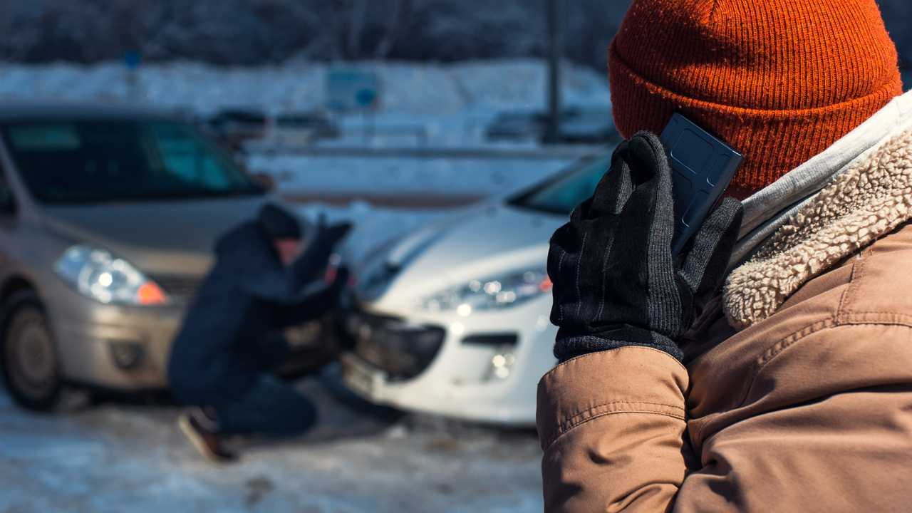 Two upset men on winter city street after car accident
