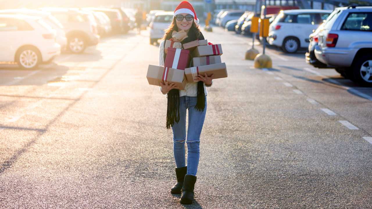 Woman walking in mall parking carrying Christmas gifts