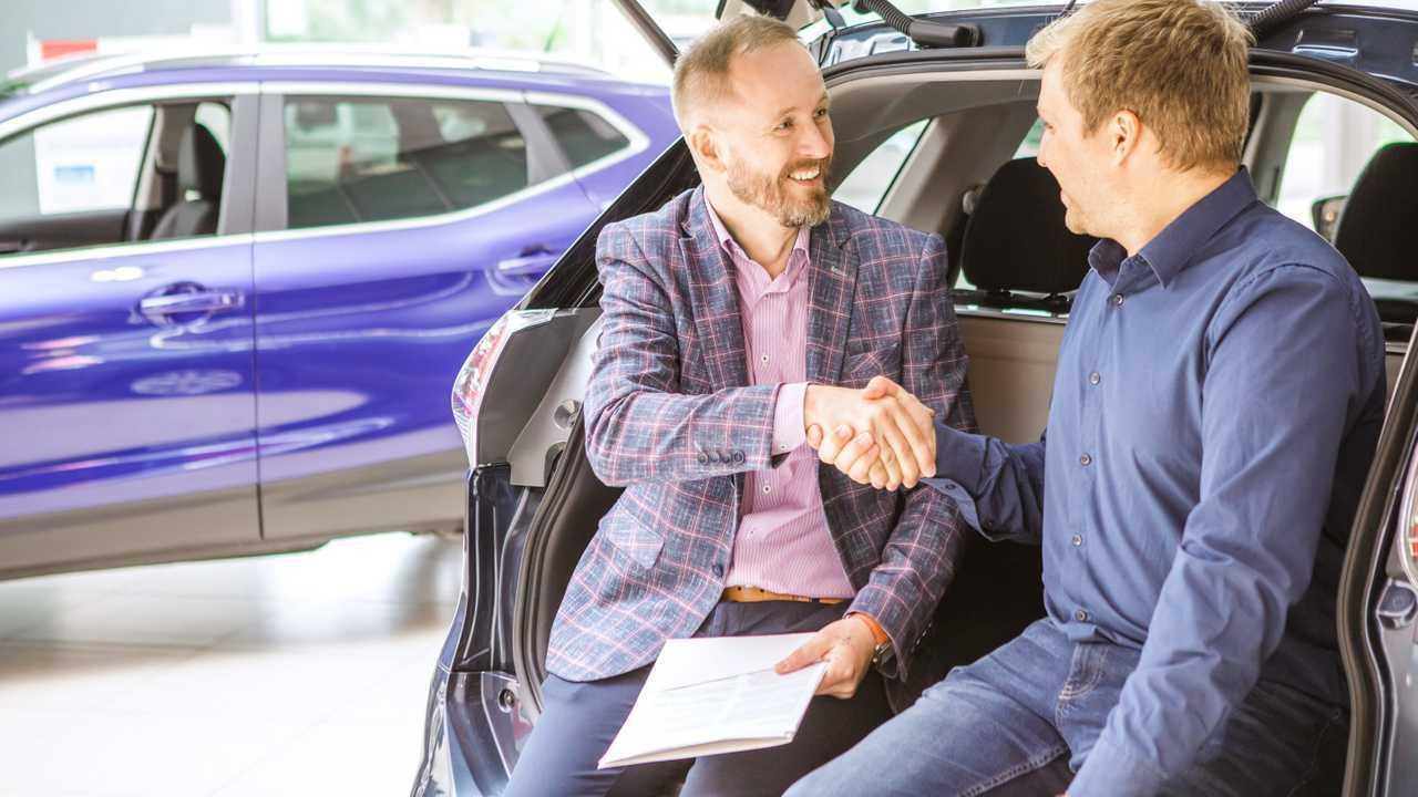 Car salesman and customer shaking hands on the showroom floor