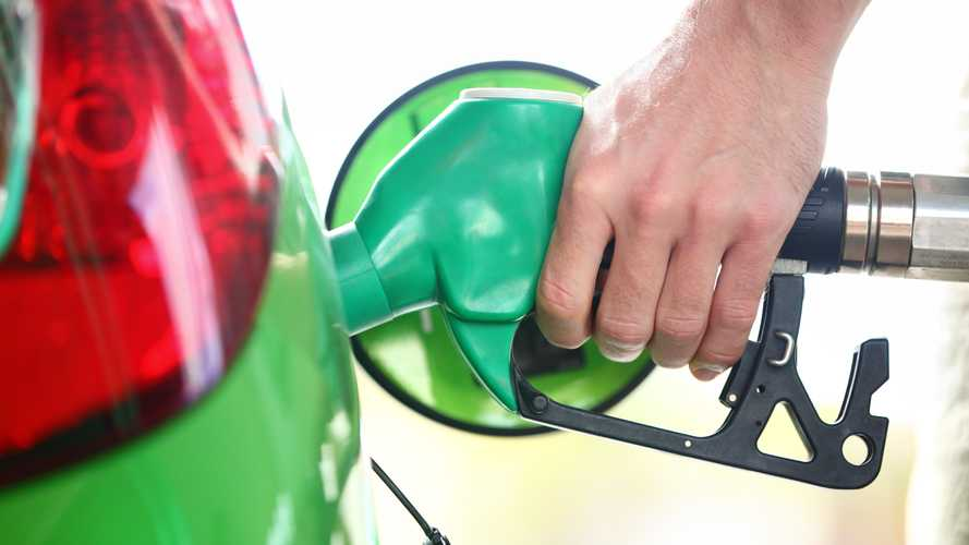 Man filling fuel in green car holding nozzle