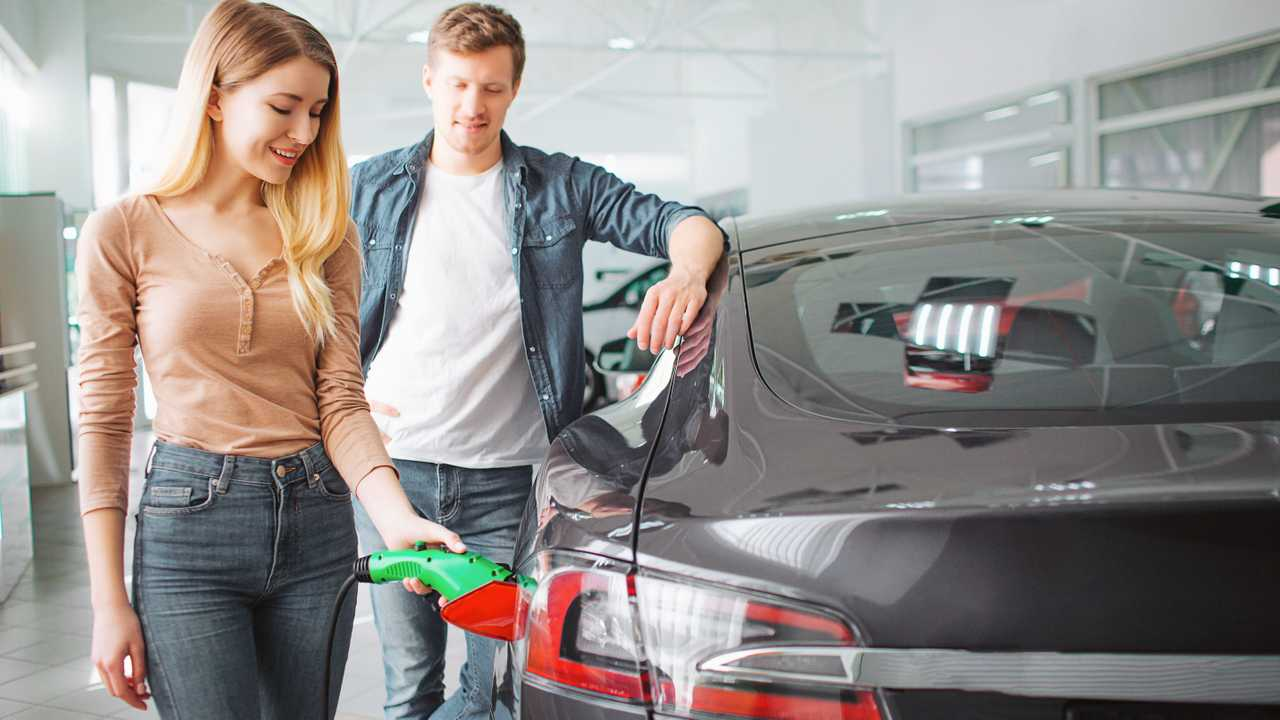 Young couple buying first electric car in the showroom