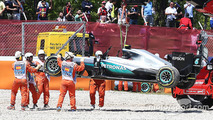 Mercedes AMG F1 is craned away from the gravel trap at the start of the race