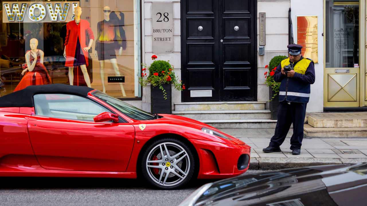 Parking attendant writing a ticket for a Ferrari in London