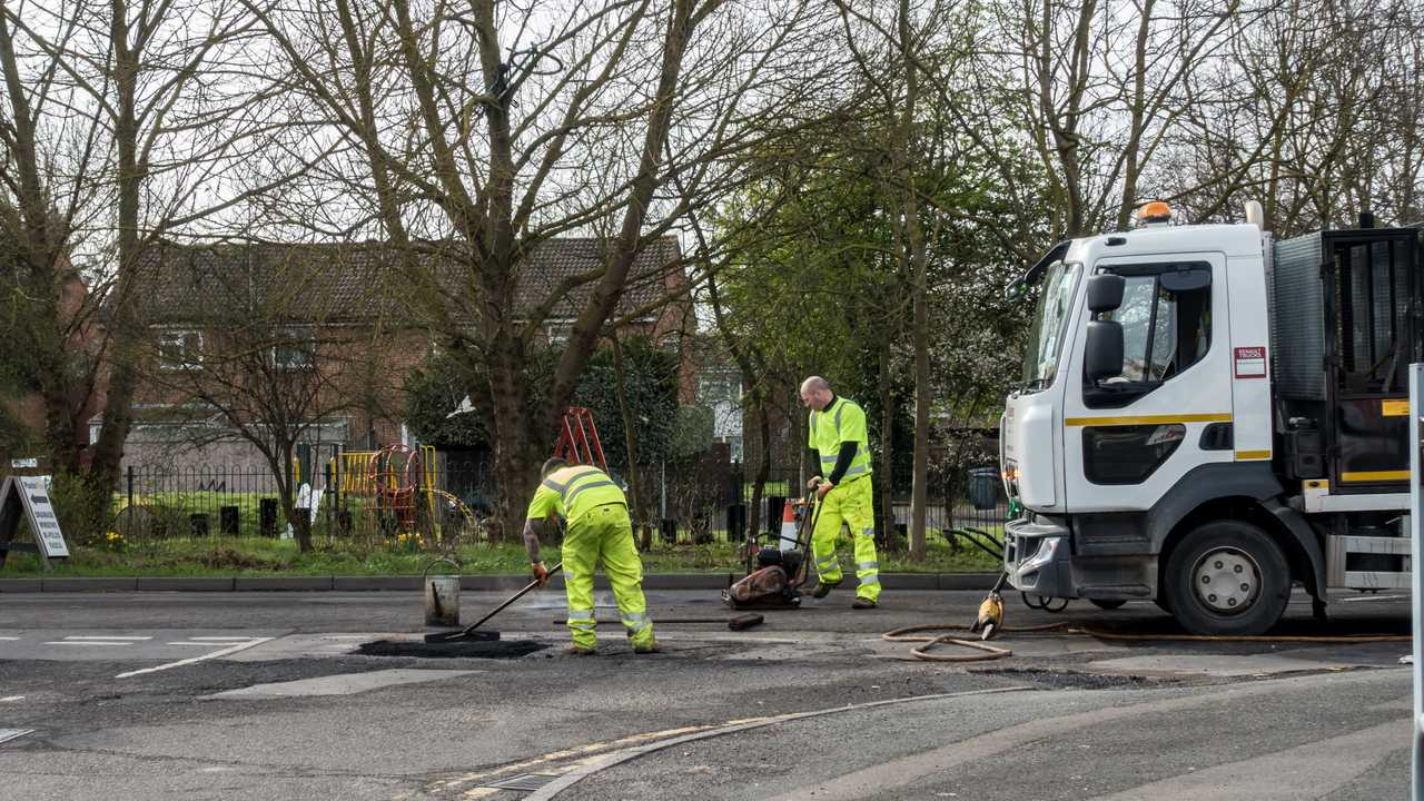 Workmen fix potholes in the road in Reading UK