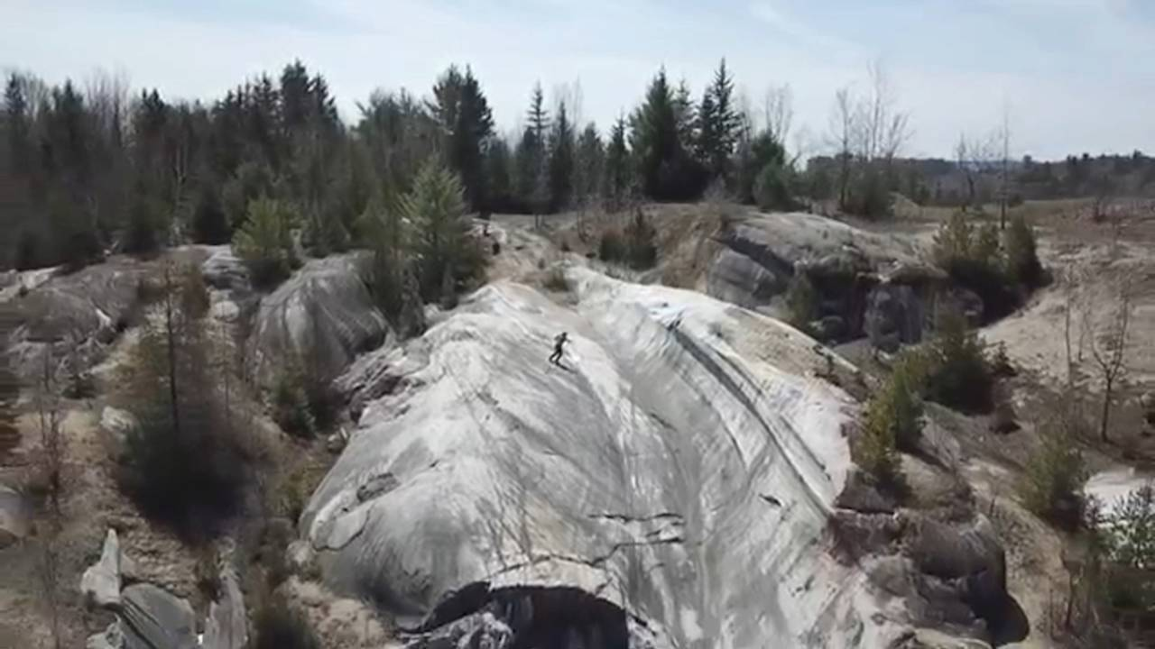 A drone shot of a halfpipe-esque section of rock