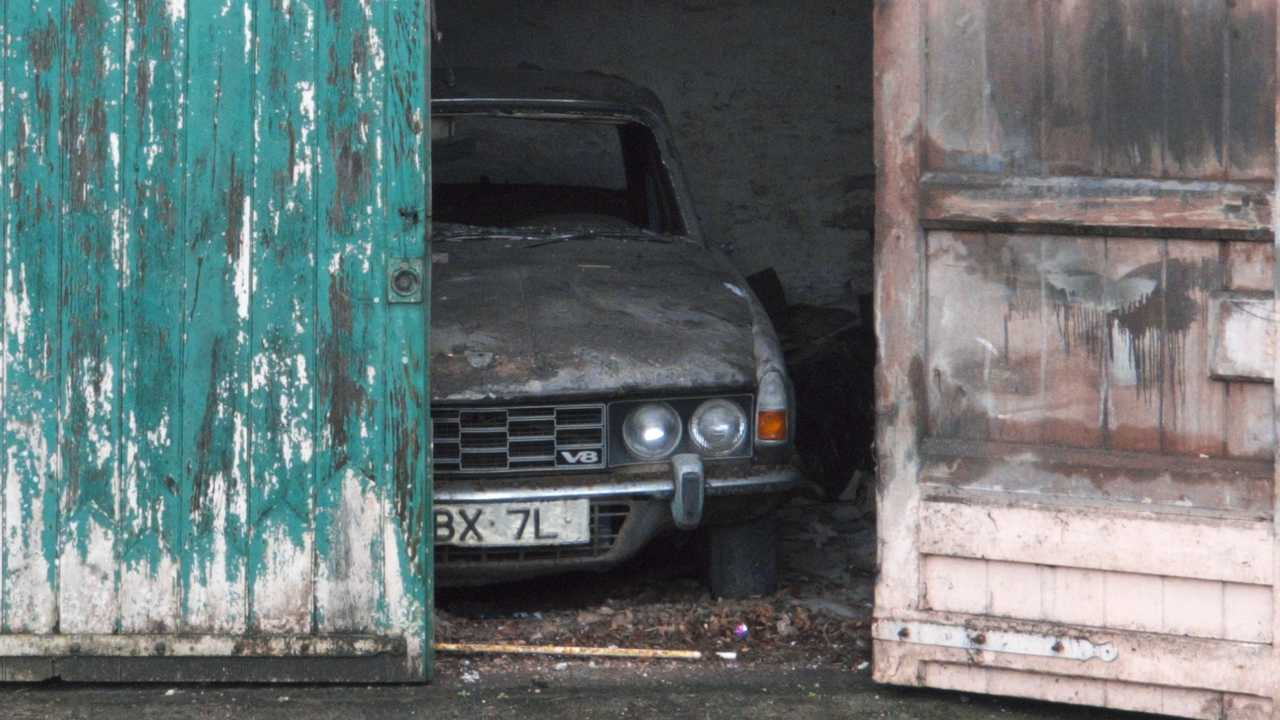Distressed Rover 3500 (P6) in a derelict garage in Laugharne Carmarthenshire Wales UK