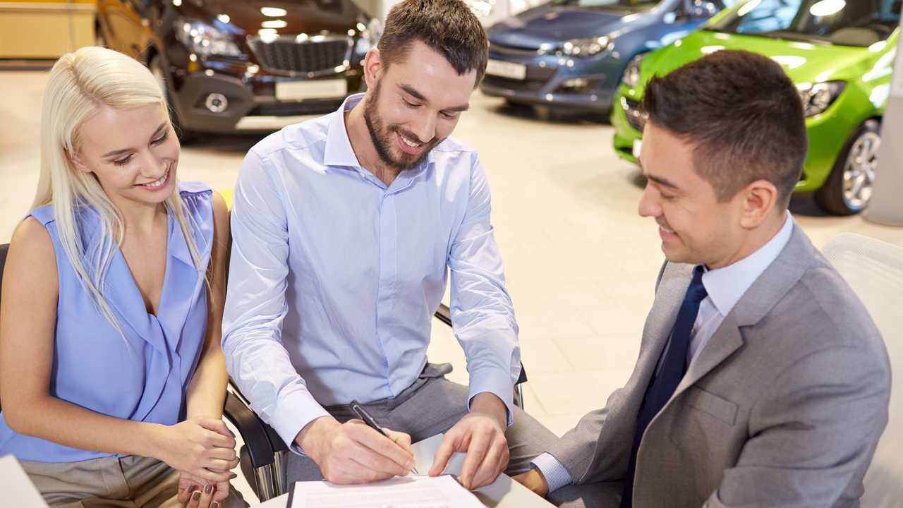 Couple with dealer buying car and signing documents