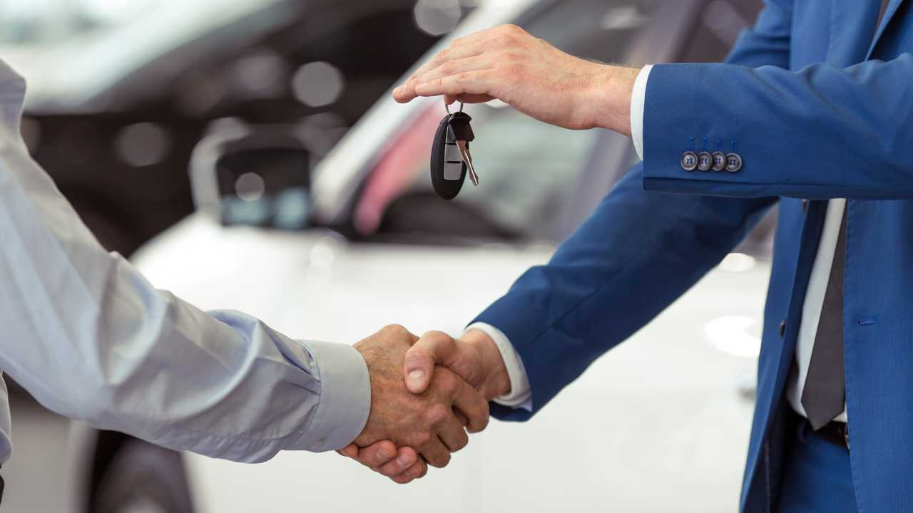 Handshake of car buyer and salesman who is handing over the keys