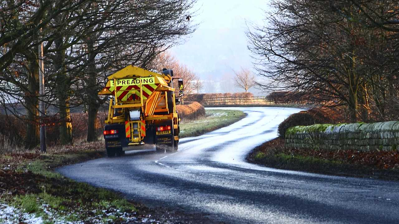 Council gritter spreading salt on a rural road in Wharfedale Yorkshire England