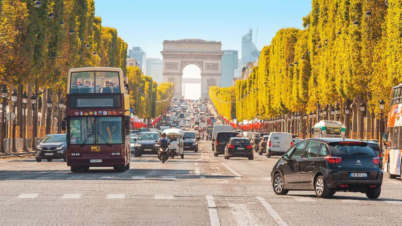 Buses and cars drive along Avenue Champs Elysees in Paris France