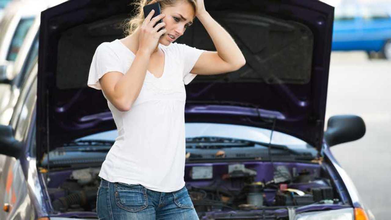 Woman using phone while looking at broken down car