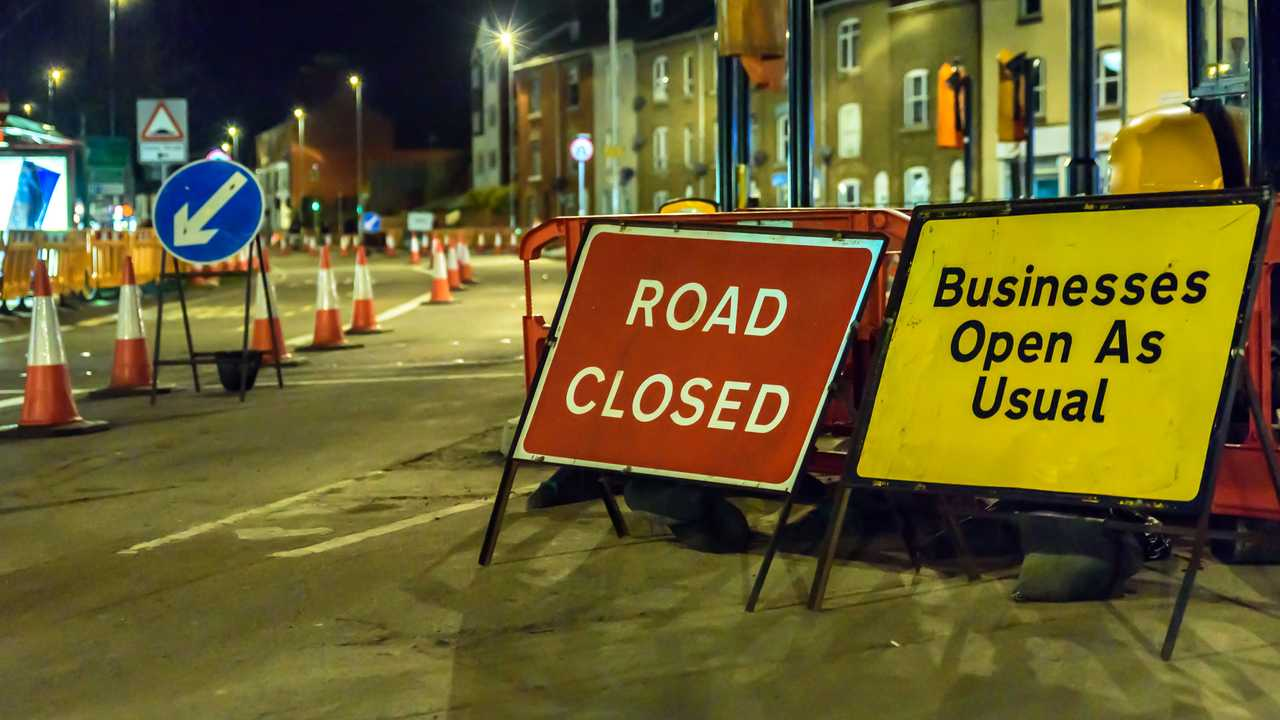 Road Closed and Business Open As Usual UK roadworks signs in London