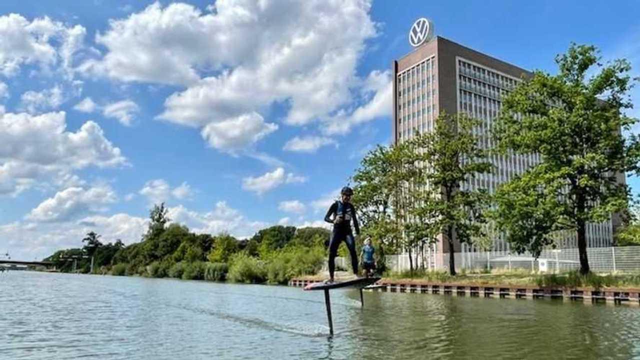 Hebert Diess cavalca la e-surfboard di Audi davanti allo stabilimento Volkswagen di Wolfsburg
