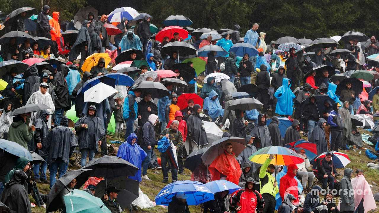 Fans under umbrellas during a red flag period at Belgian GP 2021