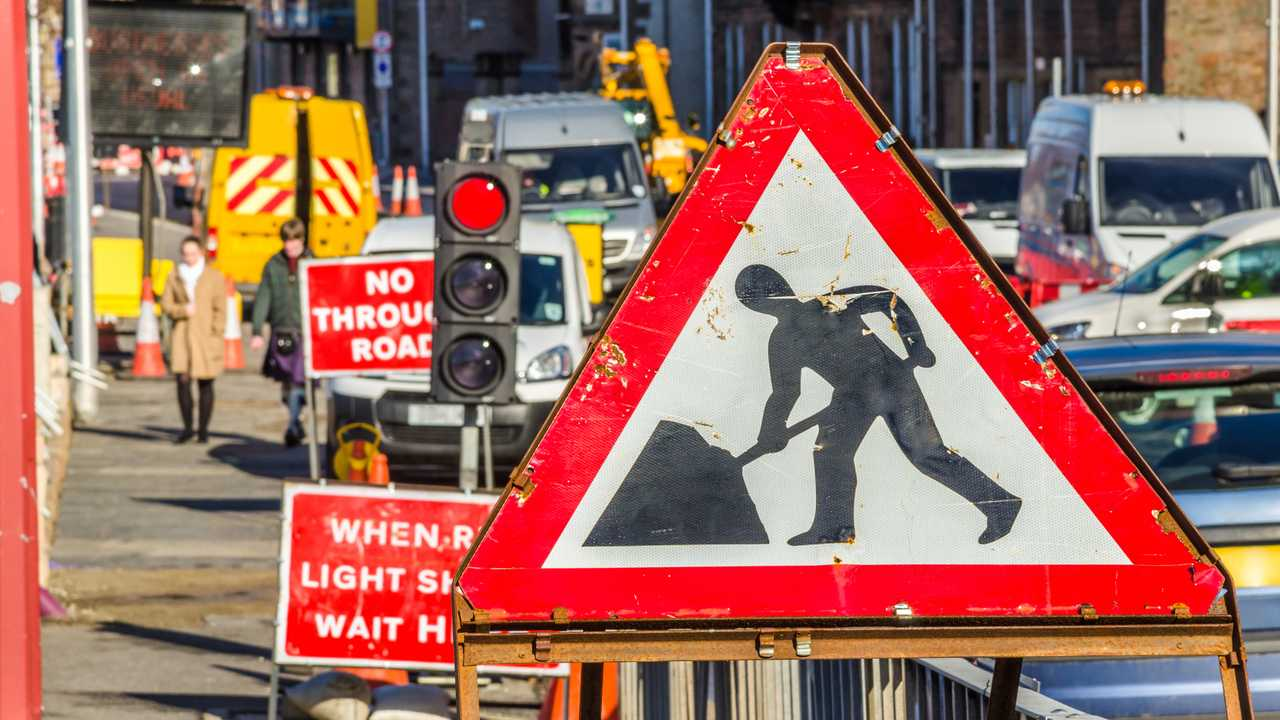 Old roadworks sign on a busy road in Scotland