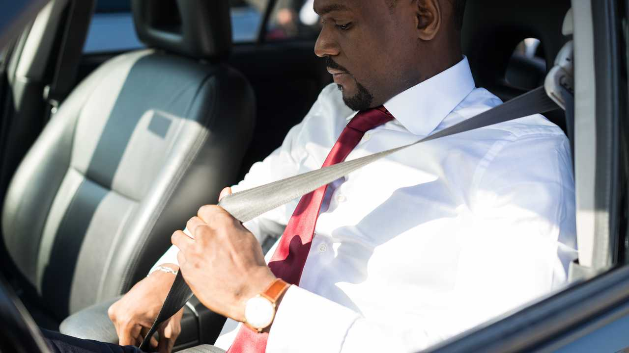 Man fastening the seatbelt in his car